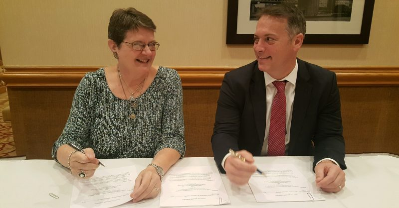 Suzanne Johnson, LCUSA president, signs a contract with Josiah Mooney and his consulting firm to begin to make the Ladies of Charity Caregiving Project a reality.